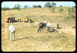 Primary view of object titled '[Cowboys, a Horse, and Industrial Vehicles on a Hillside]'.