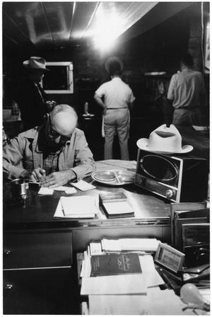 Primary view of object titled '[Watt Matthews at a Desk inside the Matthews Ranch Cookshack]'.