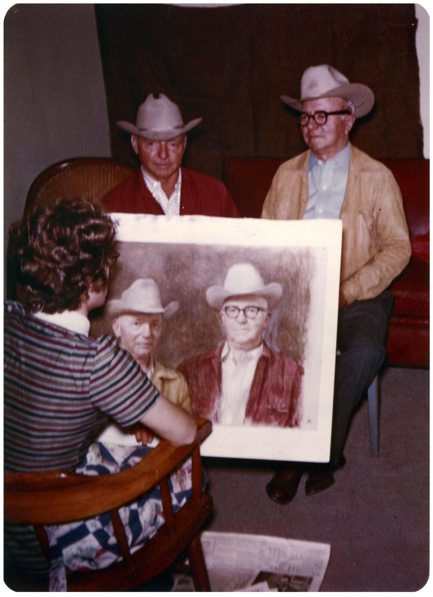 [Allison Joy with a Portrait of the Two Men Sitting in Front of Her]                                                                                                      [Sequence #]: 1 of 2