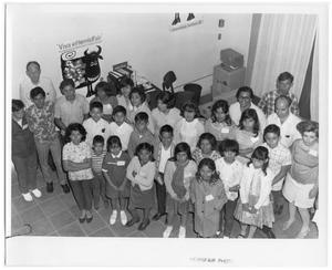 Primary view of object titled 'Children and adults posing for an indoor group picture at HemisFair '68'.