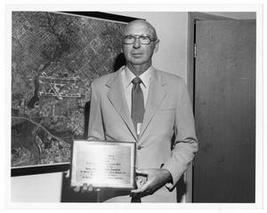Primary view of object titled '[Dallas Love Field Airport : Unknown Man Holding Plaque]'.