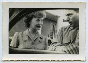 Primary view of object titled '[A Man and Woman Stand Next to a Car]'.