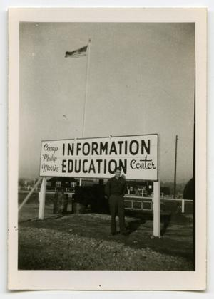 Primary view of object titled '[A Soldier Standing Under the Camp Sign]'.