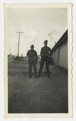 Primary view of [Man Near Another Holding a Rifle]