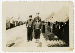 Primary view of object titled '[Three Men Between Rows of Tents]'.