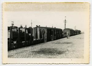Primary view of object titled '[A German Soldier Walking Along Line of Rail Cars]'.
