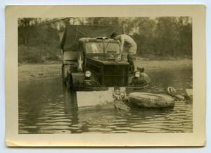 Primary view of object titled '[A Soldier Works on a Transport Truck]'.
