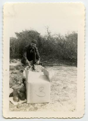 Primary view of object titled '[Photograph of a Soldier Unpacking a Box]'.