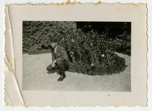 Primary view of object titled '[Man Kneeling at Flowerbed]'.