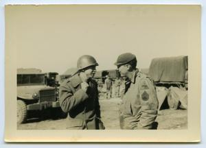 Primary view of object titled '[Two Soldiers Talking Near Transport Trucks]'.
