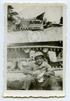 Primary view of object titled '[A Soldier Sits Next to a Tank]'.