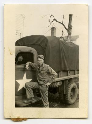 Primary view of object titled '[Photograph of Soldier by Army Truck]'.