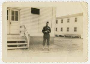 Primary view of object titled '[Soldier Near Double Door Building]'.