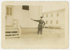 Primary view of object titled '[Man Shooting Pistol In Front of Building]'.