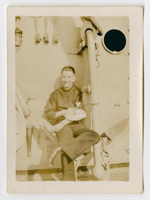 Primary view of object titled '[Photograph of a Sailor Sitting on an Anchor]'.