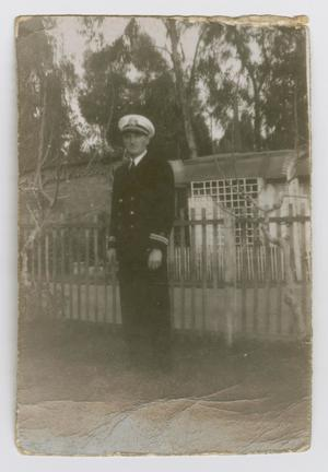 Primary view of object titled '[Photograph of a Navy Officer by a Fence]'.