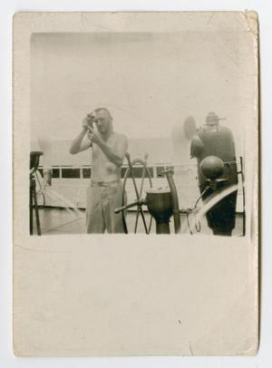 Primary view of object titled '[A Sailor Taking Measurements Behind a Wheel]'.