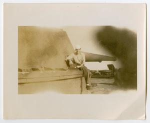 Primary view of object titled '[Photograph of a Sailor Sitting on a Gun Turret]'.