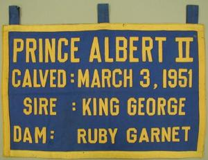 "[Blue canvas and yellow felt banner that states: ""PRINCE ALBERT II CALVED: MARCH 3, 1951]"