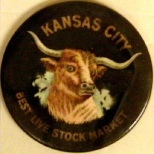 "Primary view of object titled '[Black button with image of a longhorn in the center that states: ""KANSAS CITY BEST LIVE STOCK MARKET""]'."