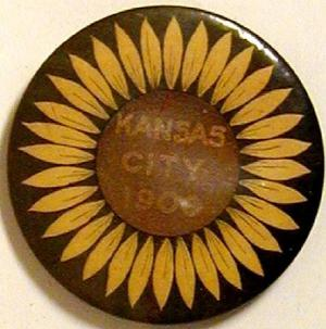 "[Button with a sunflower painted on the it and states: ""KANSAS CITY 1900""]"