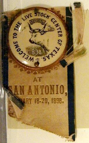 "Primary view of object titled '[Button with ribbonreads ""WELCOME TO THE LIVE STOCK CENTER OF TEXAS, SOUVENIR, 1898""]'."