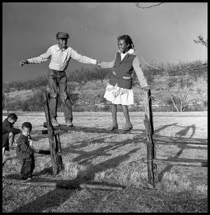 Primary view of object titled '[Bailey Woods and Sue Antoinette Emory Standing on Fence]'.