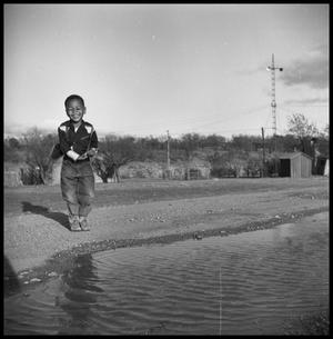 Primary view of object titled '[Child By a Dirt Road and a Watery Ditch]'.