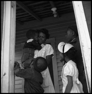 [Children Standing with a Woman in a Doorway]