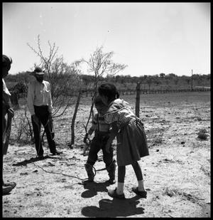 Primary view of object titled '[Jack Newcomb Holding a Rope Attached to a Child]'.