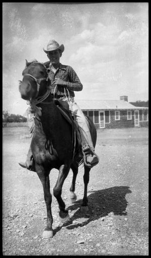 Primary view of object titled '[Boy on Horseback in Front of Brick Building]'.