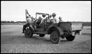Primary view of object titled '[Rear View of Ranchers Sitting on a Truck]'.