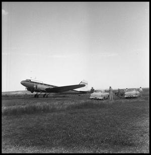 [Airplane in a Field with Three Cars and People]