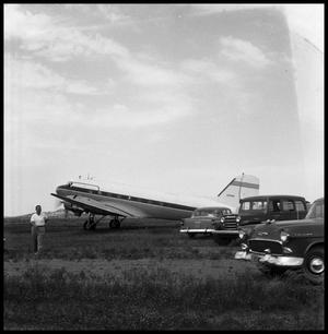 Primary view of object titled '[Airplane in a Field with Three Cars and a Man]'.