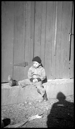 Primary view of object titled '[Boy Sitting on a Concrete Foundation]'.