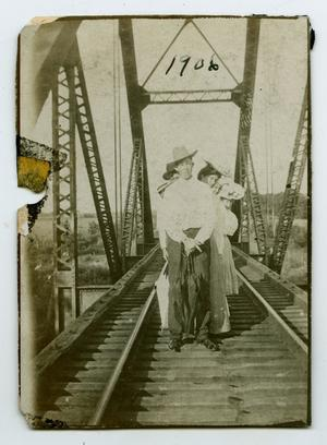 Primary view of object titled '[Photograph of Friends Walking on the Rowlett Creek Railroad Bridge]'.