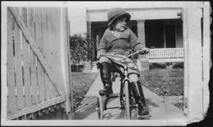 [Photograph of Mary Jones riding her tricycle on a sidewalk]