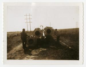 Primary view of object titled '[Men Standing By Long Metal Poles #2]'.