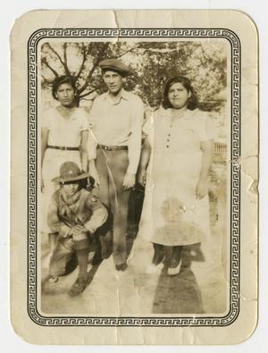[Photograph of Three Adults and Child Posing Outside]