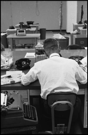 Primary view of object titled '[Man Working at Desk at Beaumont Enterprise #9]'.