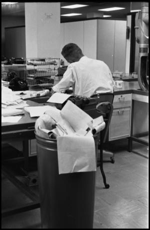 Primary view of object titled '[Man Working at Desk at Beaumont Enterprise #1]'.