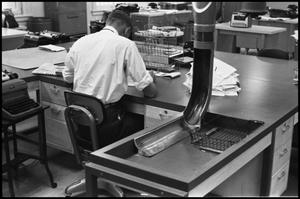 Primary view of object titled '[Man Working at Desk at Beaumont Enterprise #10]'.
