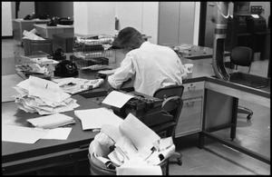 Primary view of object titled '[Man Working at Desk at Beaumont Enterprise #5]'.