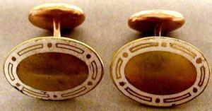 Primary view of object titled '[A pair of oval shaped gold cuff links with a white stripe around the edge]'.
