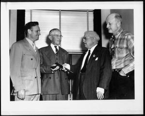 Primary view of object titled '[Albert Peyton George holding a gun, next to three unidentified men]'.