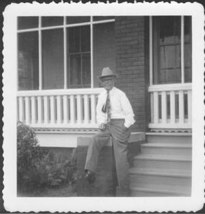 [Mr. Albert George seated on the brick rail in front of the ranch house]