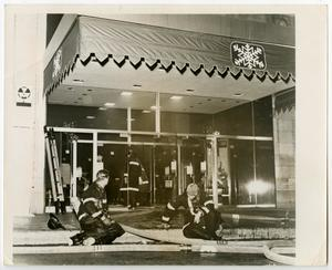 Primary view of object titled '[Two Firefighters Sit on Curb in Front of Neiman-Marcus]'.