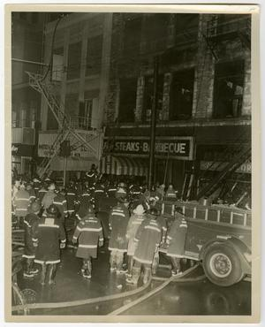 Primary view of object titled '[Crowd of Firefighters on a Rescue Operation at Business Strip]'.