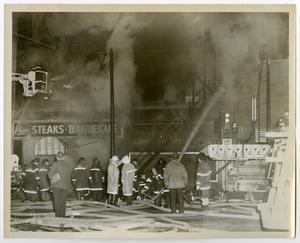 Primary view of object titled '[Row of Firefighters in Front of Smoking Building]'.