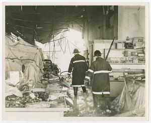 Primary view of object titled '[Two Firefighters Walk Through a Destroyed Store]'.